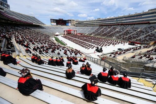 Photo showing groups of graduates spread out in the stands and on the field.