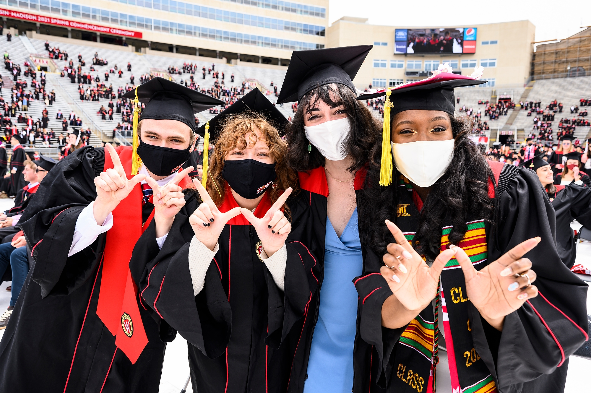 """Four graduates flash the """"W"""" with their hands."""