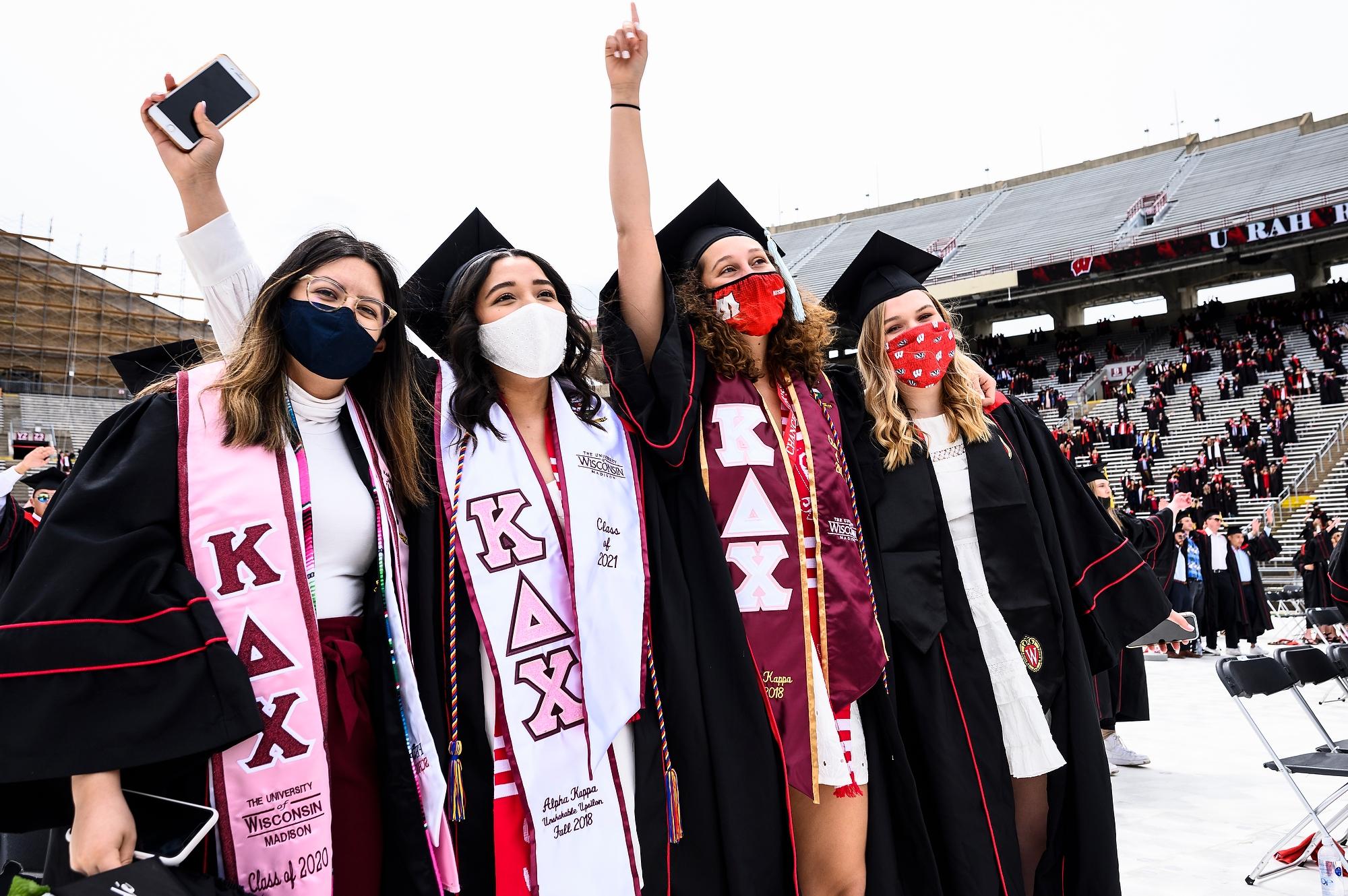 "Graduates wearing Kappa Delta Chi stoles join arms to sing ""Varsity"""