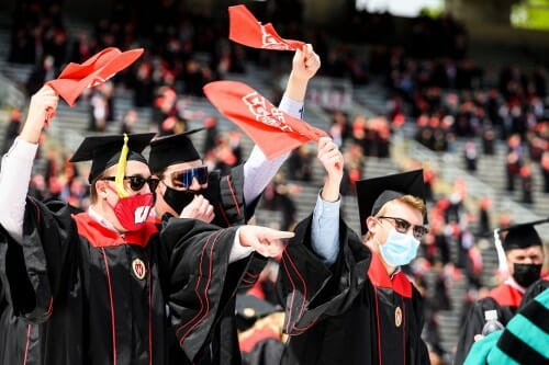 Photo of graduates waving the red rally towels.