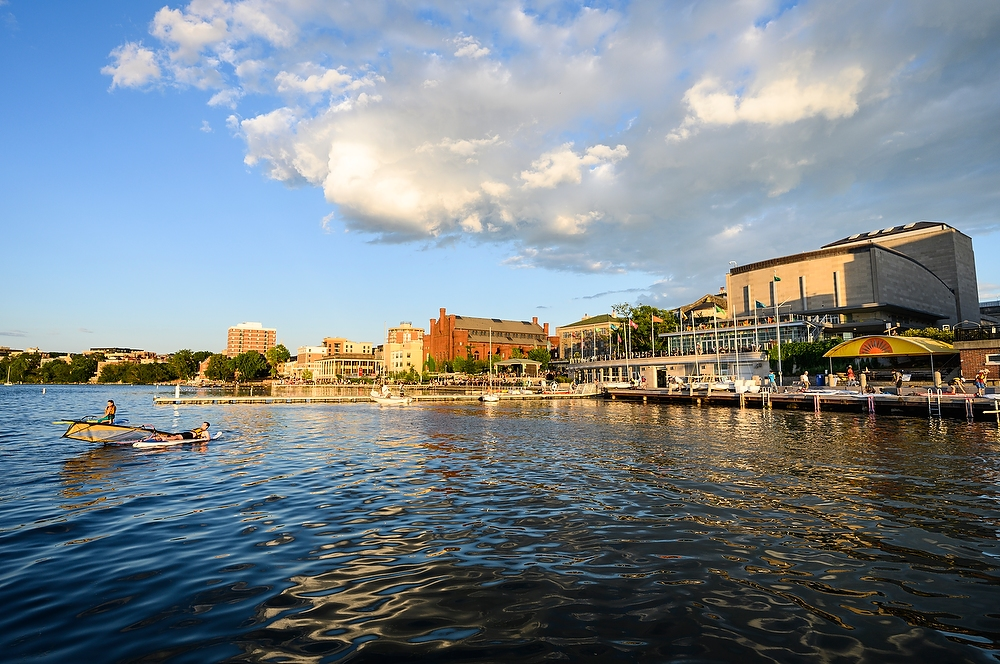 A blue sky with a few clouds is reflected in Lake Mendota with the Terrace in the background.