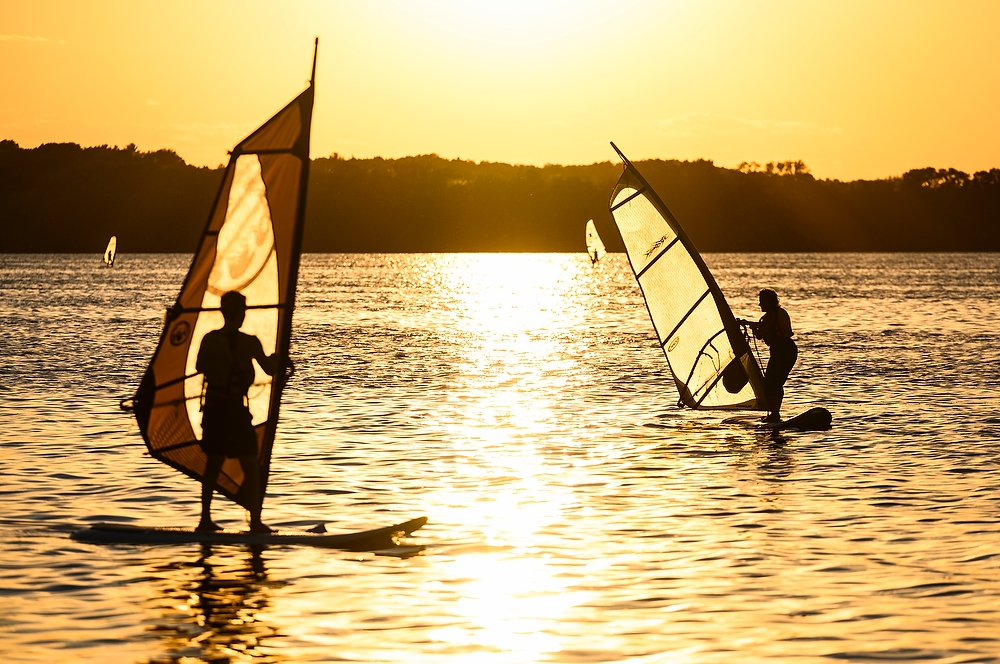 Two wind surfers on the dappled surface of the lake.