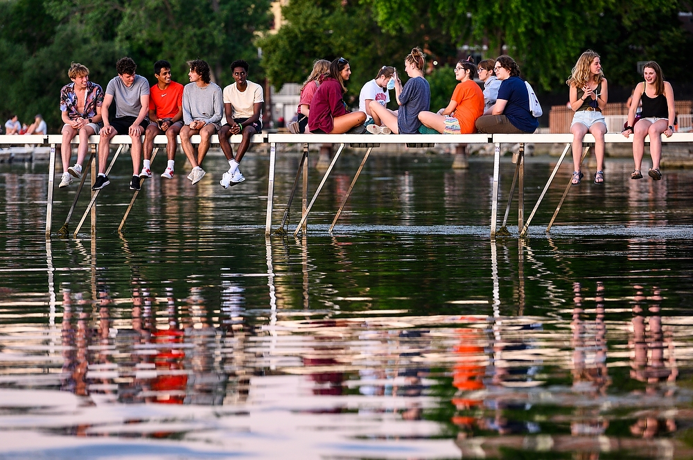 Students sit on a pier, talking and laughing.