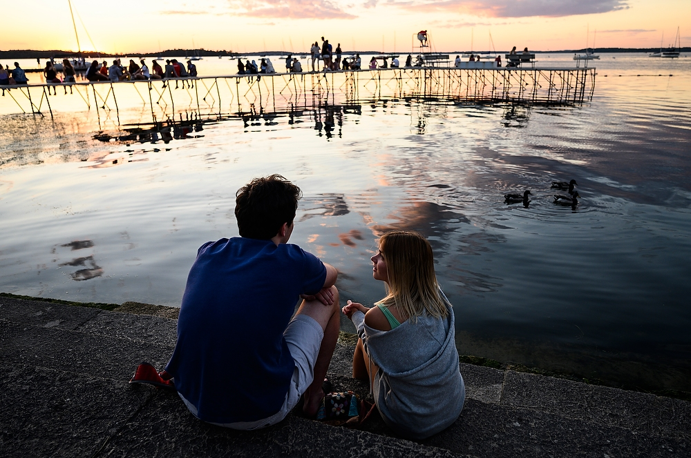 Two people look out over the lake, with a pier in the background with more people on it.
