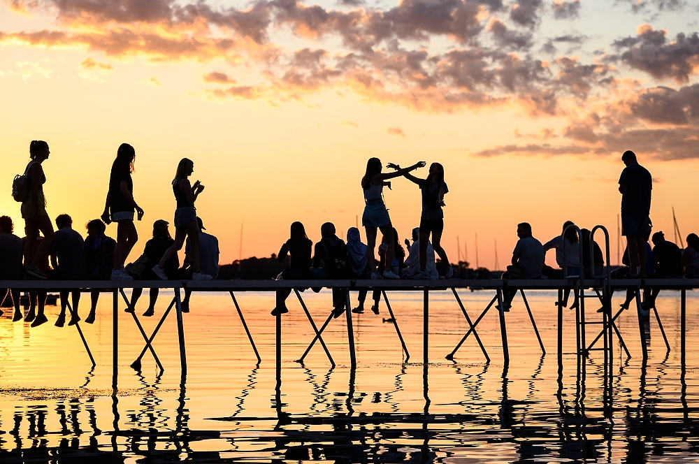 People are silhoutted by the setting sun as they sit on a pier in Lake Mendota.