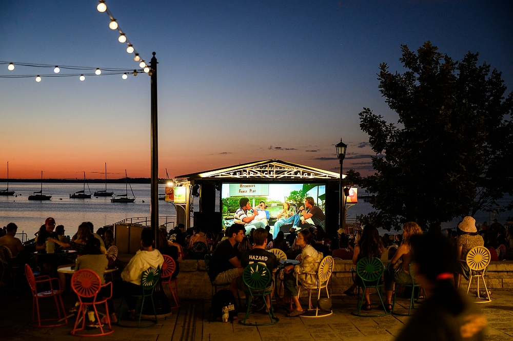 A movie is projected on a screen on the Memorial Union Terrace, with the lake in the background.