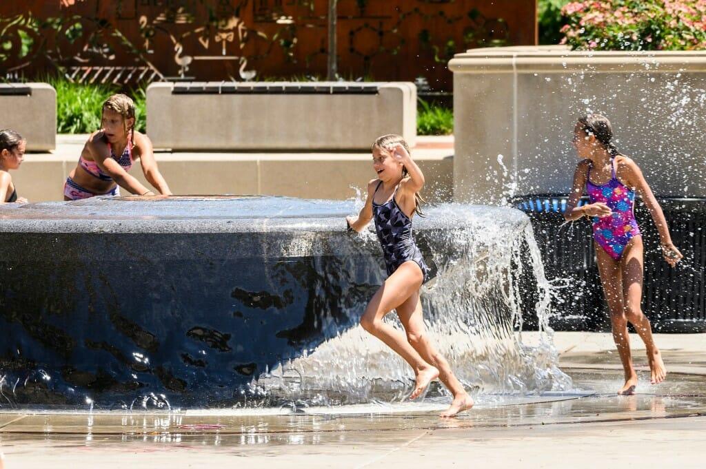 A girl runs around the fountain.