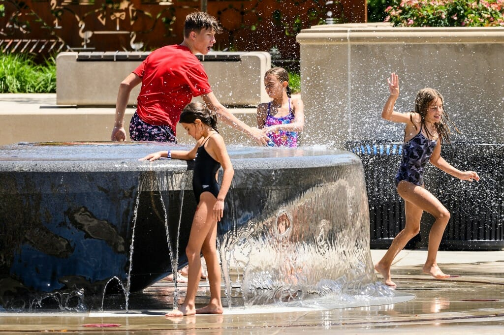 Children run around a water fountain.