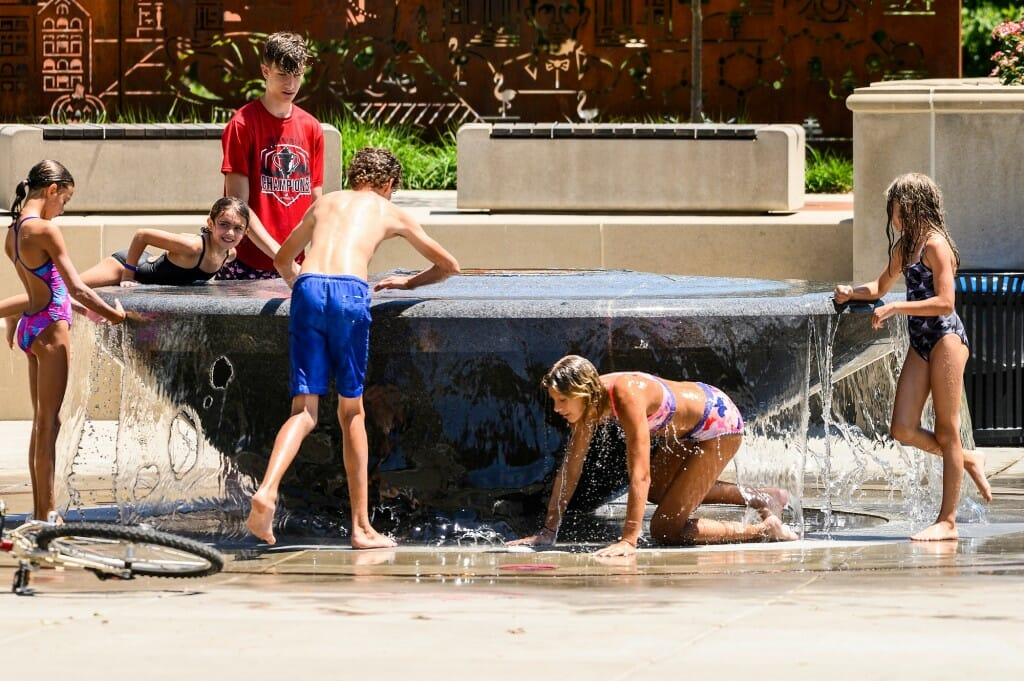 Children play with water in the fountain.