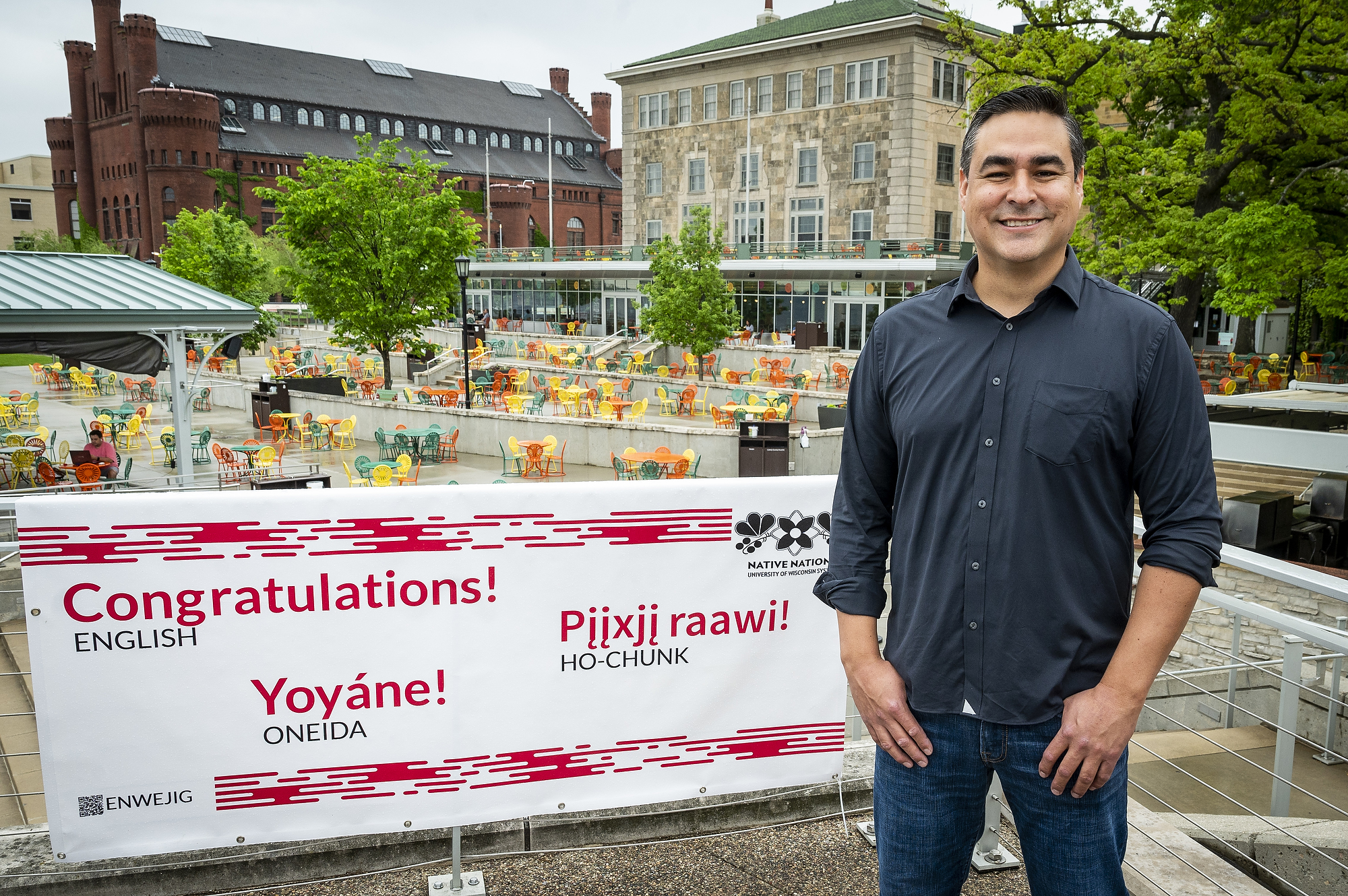 """Photo of Brian MacInnes standing next to a red and white banner on the Memorial Union Terrace with the word """"Congratulstions!"""" written in English, Oneida and Ho-Chunk."""
