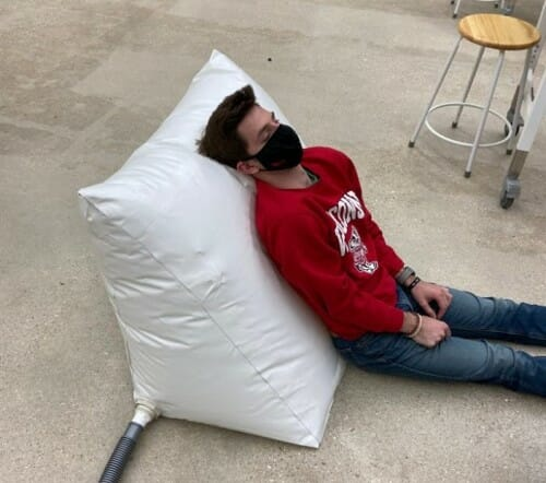 Person leaning against an inflated pillow