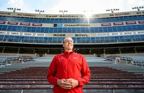 Photo of Chris McIntosh standing in the bleachers of Camp Randall Stadium.