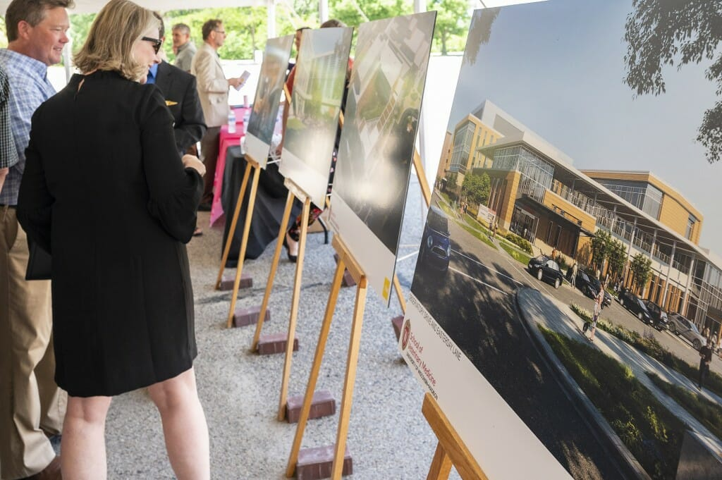 Attendees look over architectural renderings.