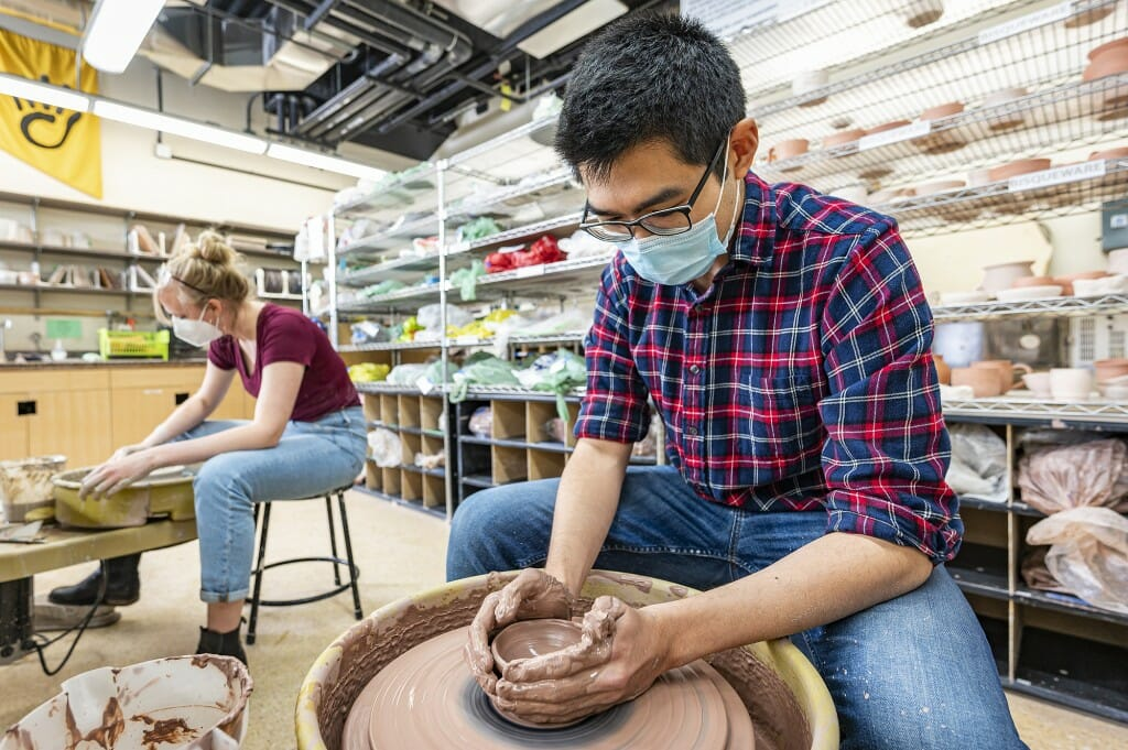 UW graduate student Andrew Sung forms clay at a pottery wheel.