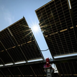The sun shines down on a silhouetted row of solar panels.