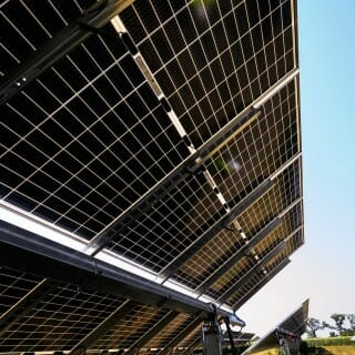 """The underside of a row of solar panels reveals their """"bifacial"""" design. Bifacial panels absorb light on both sides: the upper side from direct sunlight, and the underside from the albedo effect, or reflected light from the ground. The latter is especially important in the winter, when snow maximizes the albedo effect. Bifacial panels add up to 20% extra energy capacity to a solar array. In addition, the albedo effect helps to melt snow off the top surface of the panels."""