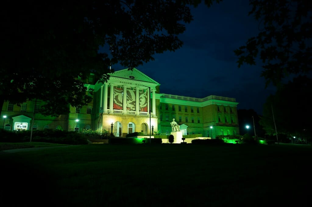 During a summer night on June 21, 2021, the University of Wisconsin-Madison illuminates the exterior of Bascom Hall and terrace plantings surrounding the Abraham Lincoln statue with green light in honor of the Milwaukee Bucks basketball team's winning of the 2021 NBA Championship the evening before. Hanging between the Bascom Hall's building columns is a graphic banner of UW-Madison mascot Bucky Badger. (Photo by Jeff Miller / UW-Madison)