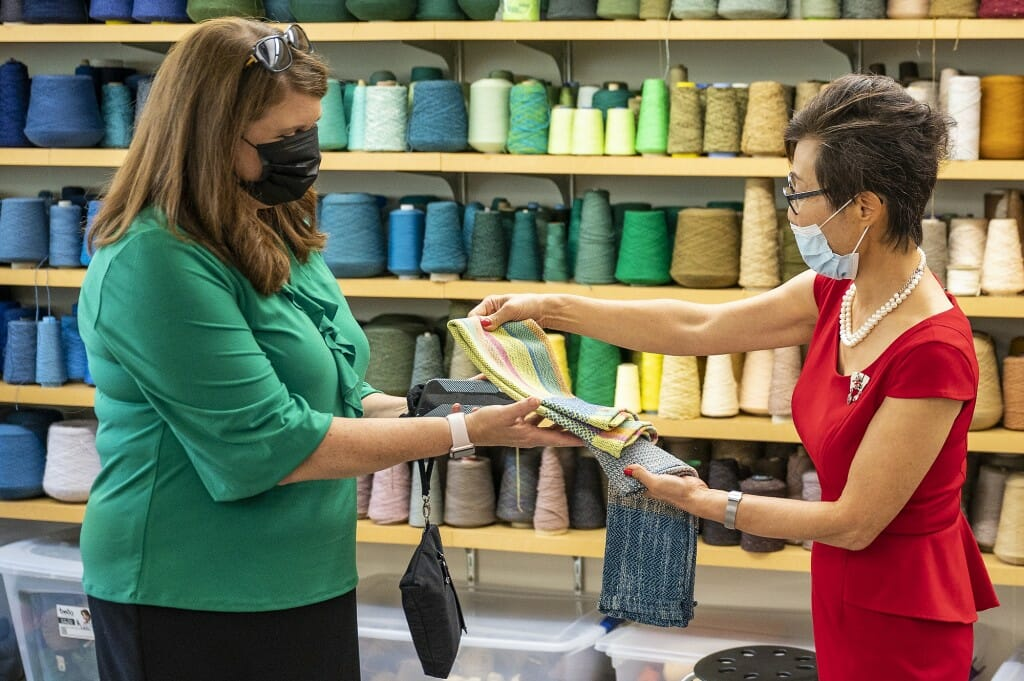 Soyeon Shim, dean of the School of Human Ecology, presents a gift of a hand towel made in the school's weaving lab to DFI Secretary Kathy Blumenfeld.