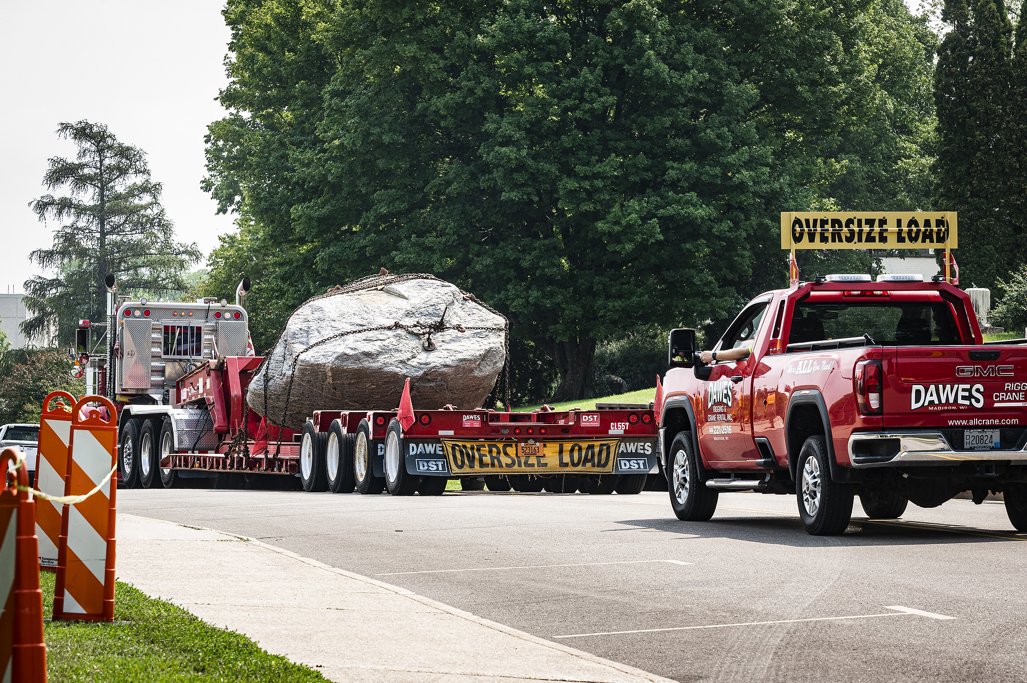 """A flatbed truck drives down the road with the rock in its bed, secured by chains. A pickup truck with the sign """"oversize load"""" follows."""