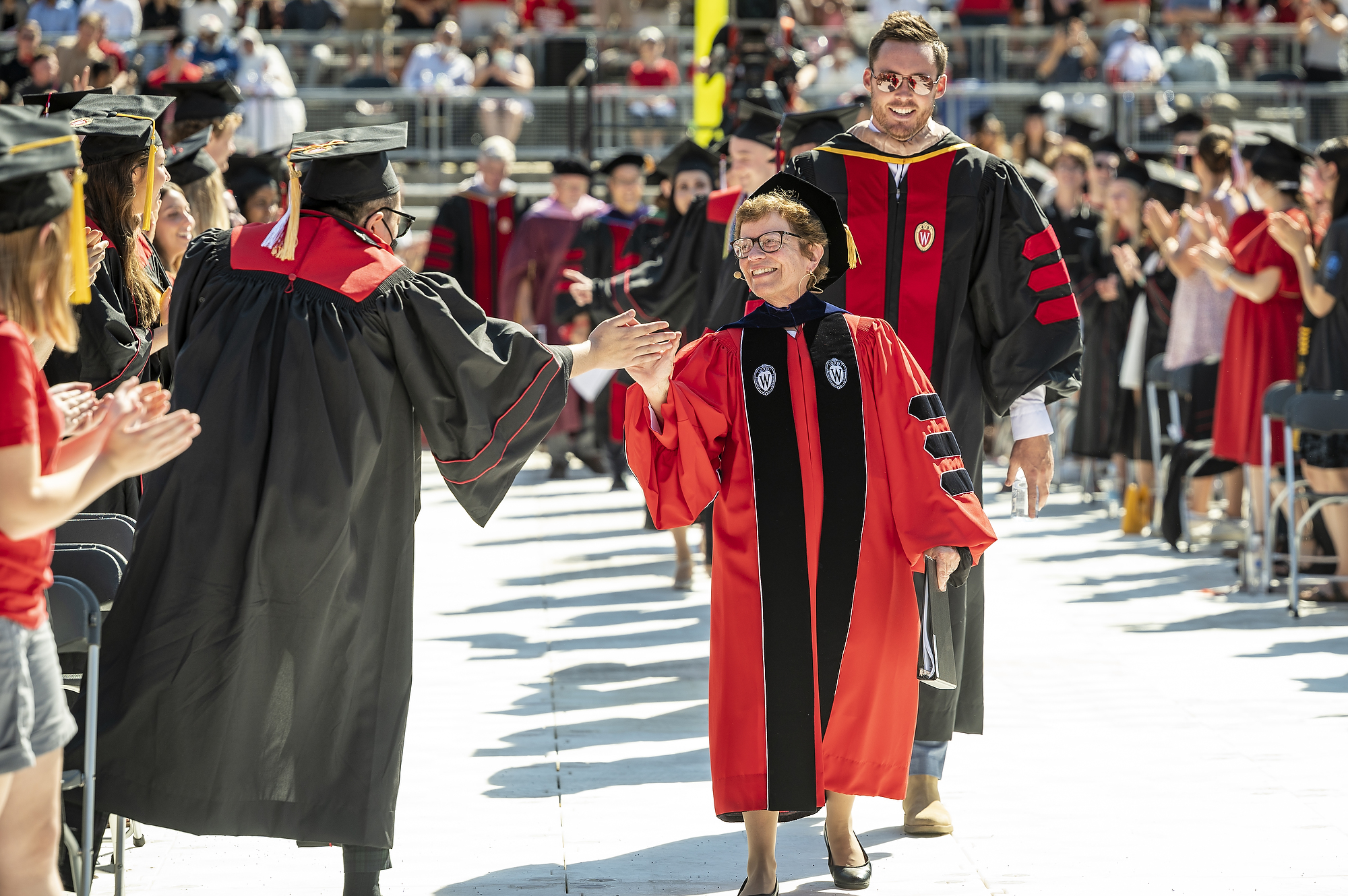 Chancellor Rebecca Blank, wearing red and black Wisconsin academic regalia, exchanges high fives with a graduate in cap and gown