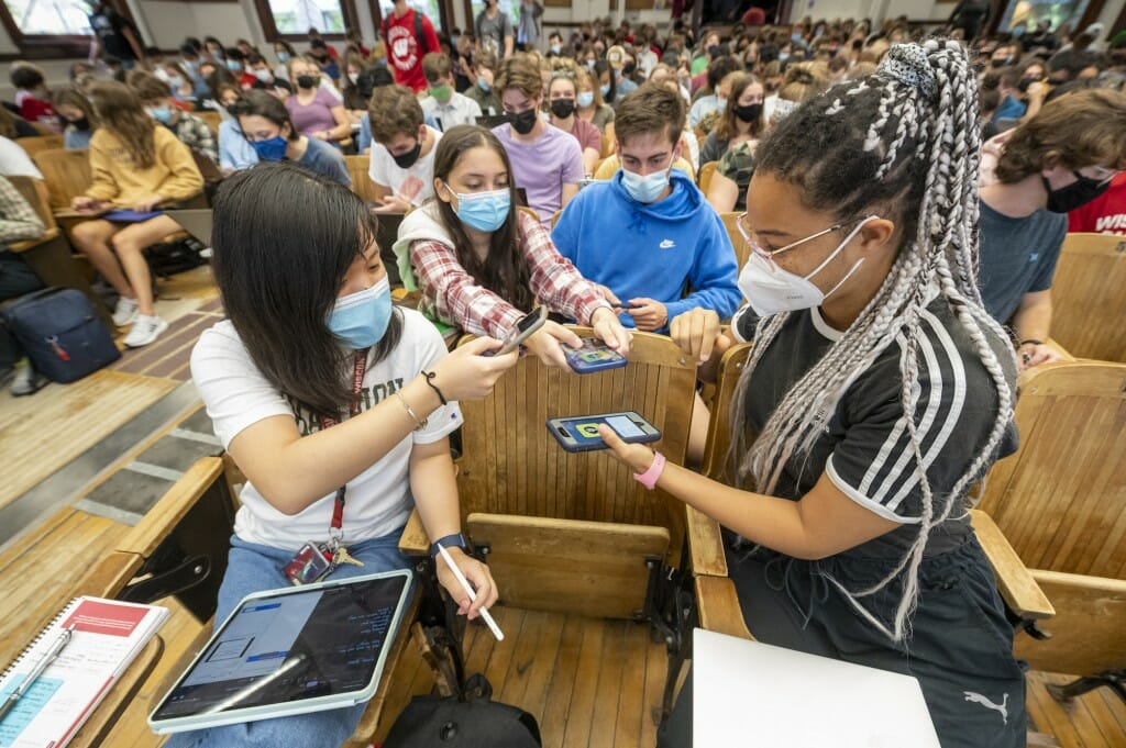 First-year students Joyce Ni, Sarah Rab, and Hannah Bertrand add each other as friends on Snapchat before the start of Chemistry 103 in Agricultural Hall.