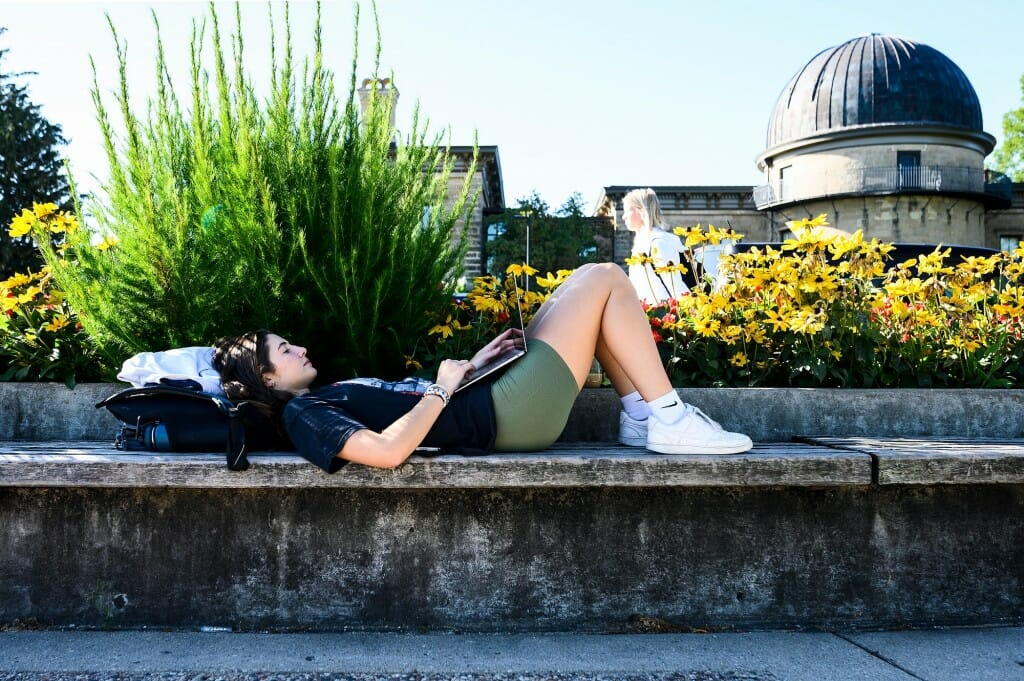 Katina Mistrioty, a recent transfer student from UW-LaCrosse, relaxes in the shade and works on her laptop computer while sitting on a bench along Observatory Hill Drive.