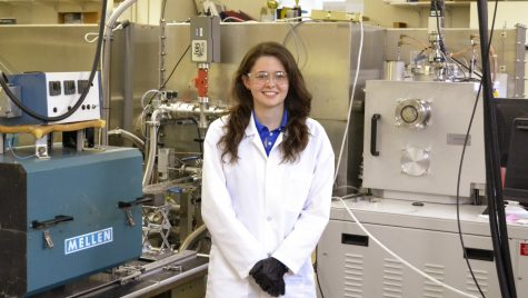Katherine Jinkins in a lab coat standing in a lab