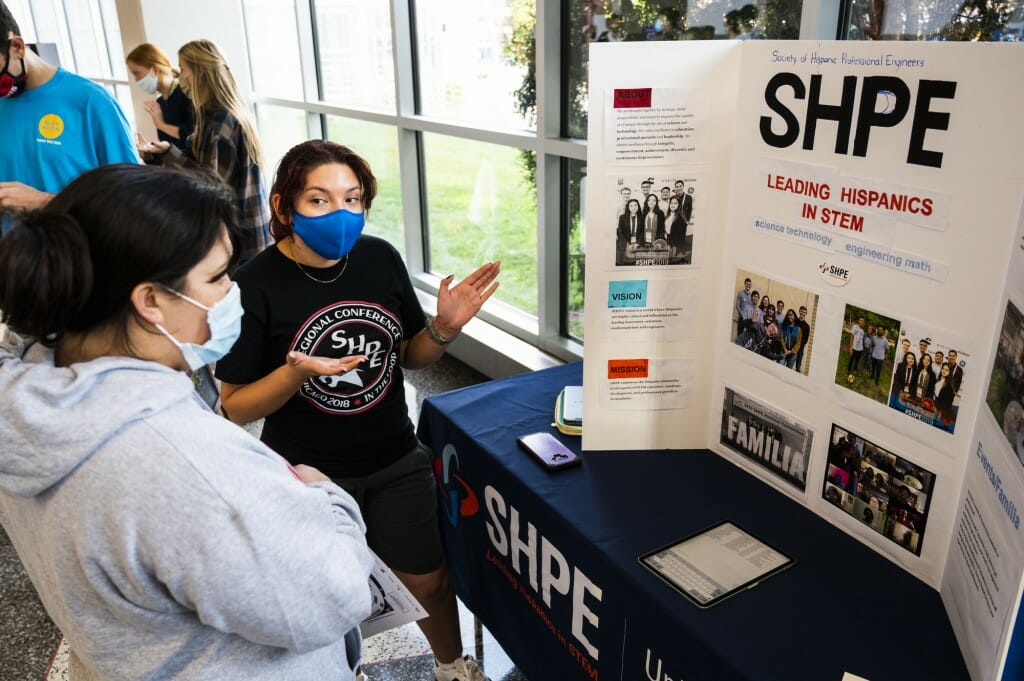 Christina Rivas, a senior, encourages a student to join the Society of Hispanic Professional Engineers.