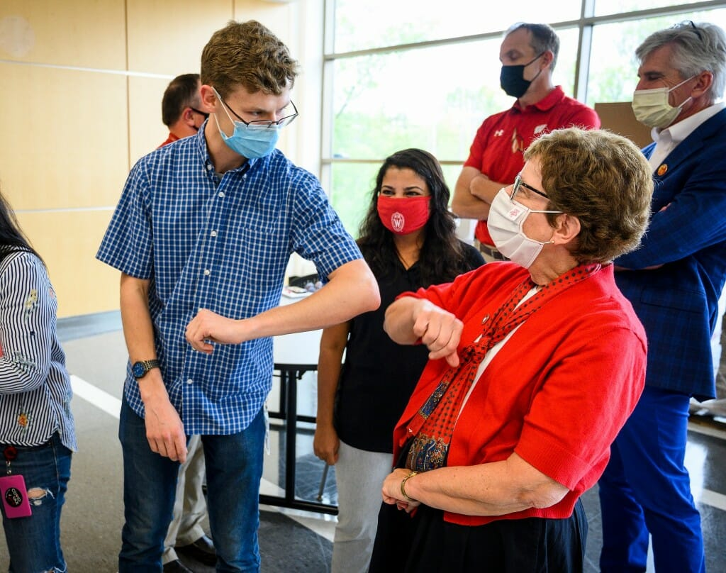 Microbiologist Jaret Schroeder uses an elbow bump to greet Chancellor Blank.
