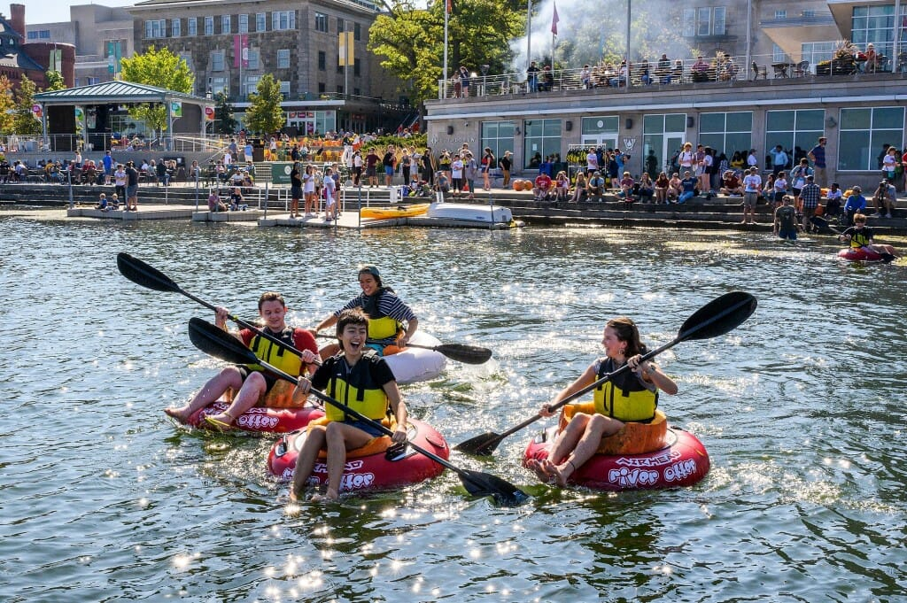 People with oars in pumpkins on the water