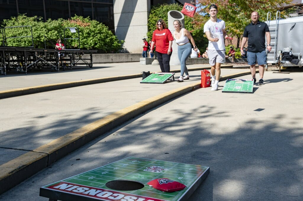 Ben Kemp and Michael Melendez play a game of UW-themed bag toss outside Union South.