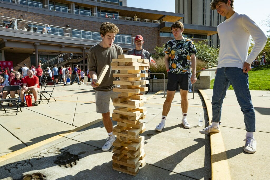 Eliiot Giffin, Sam Bradin and Sam Giffin play a game of oversized Jenga outside Union South.