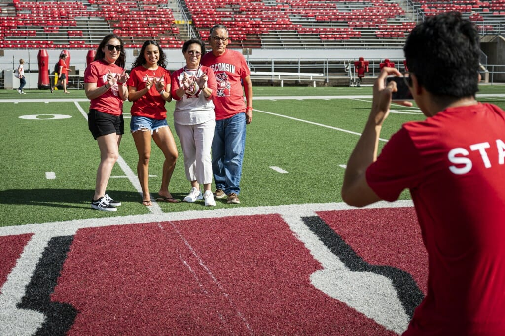 Kaila Land, along with her mother and grandparents, pose for a photo on the Motion W on the 50-yard line of the field at Camp Randall Stadium.