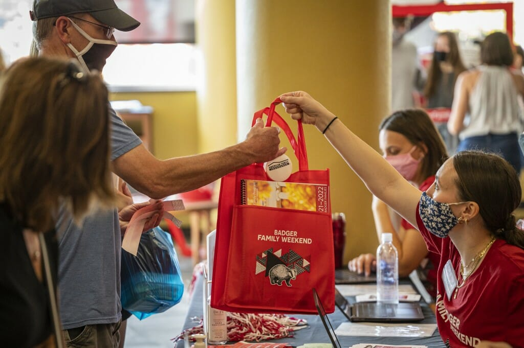 Staff members hand out bags filled with welcome gifts as families check in for Family Weekend at Union South.