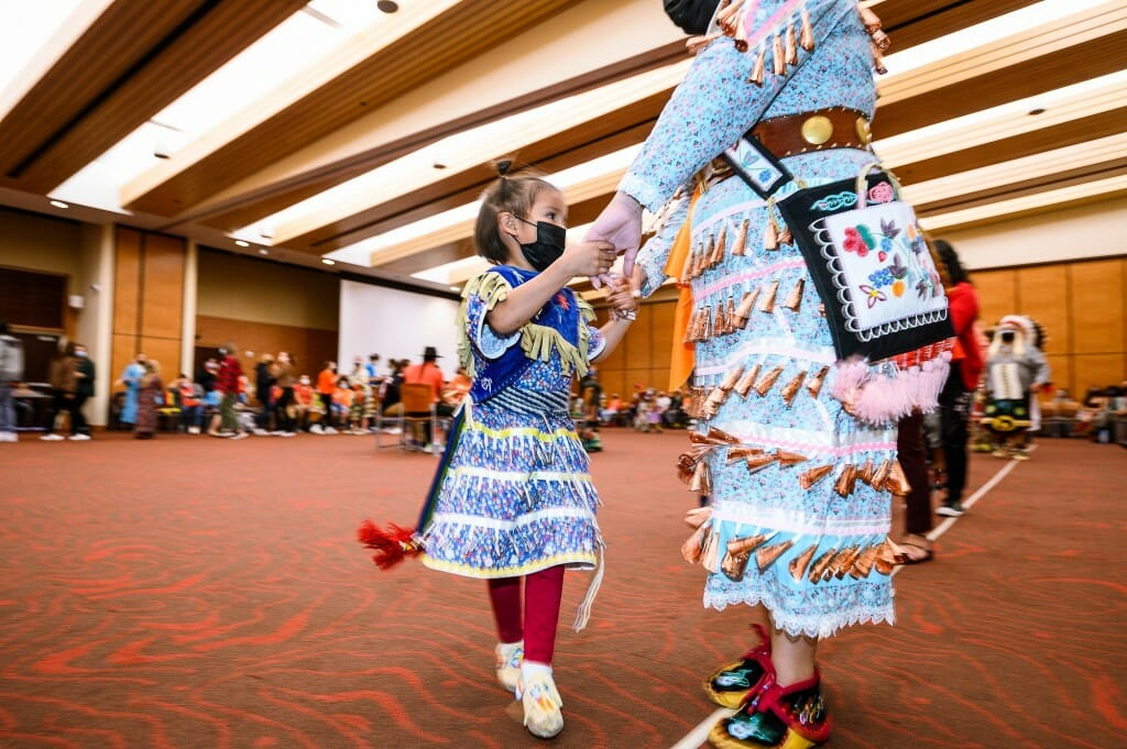 A young girl and woman, Tessa Begay of Lac Courtes Oreilles, dance during the powwow.