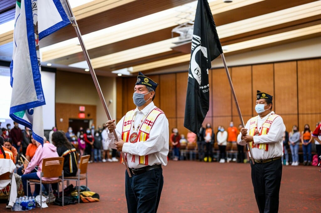 Military veterans Marlon and Marcus WhiteEagle, both of H0-Chunk Nation, enter with color guard flags.