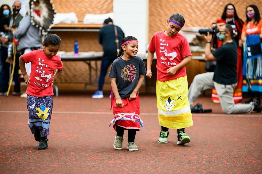 A group of young children dance.