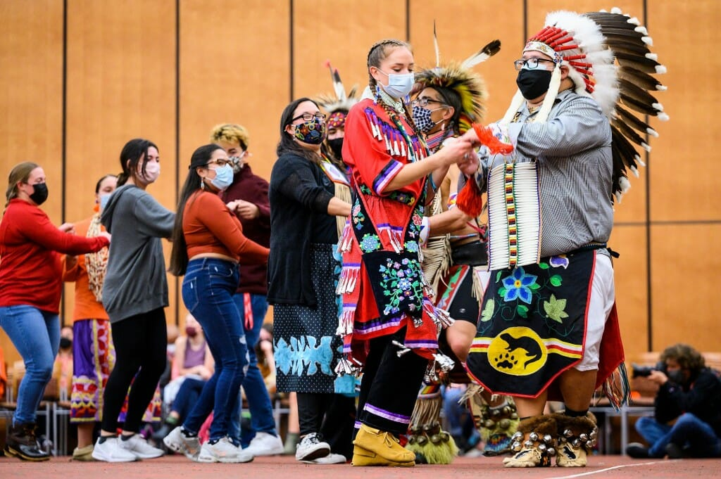 At right, UW-Madison alumni Grace Armstrong, head female dancer of Red Cliff Ojibwe, and David O'Connor, head male dancer of Bad River Ojibwe, lead a two-step community dance.