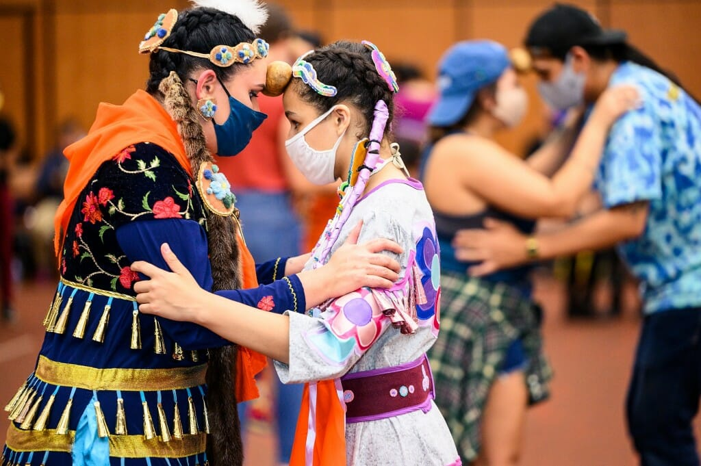 From left to right, Nbiiwakamigkwe of the Leech Lake Band of Ojibwe, and Keja Schreiber of Marten Falls First Nation, embrace for the potato dance – where two dancers hold a potato between their foreheads while attempting to dance with the beat.