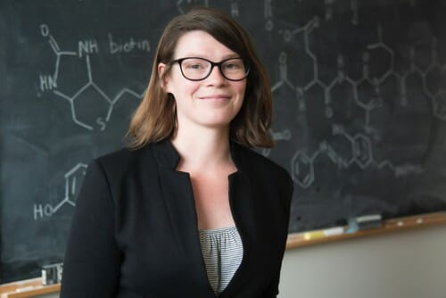 Portrait of Amy Weeks posing in front of a chalkboard