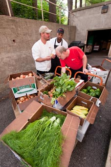Photo of three UW Housing staff surrounded by boxes of peppers, squash, fennel, onions, tomatoes and other fresh produce.
