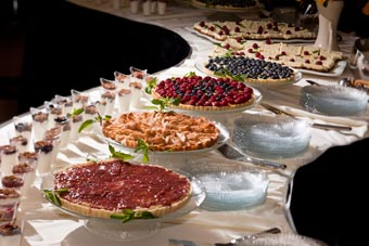 Photo of a table full of fruit-filled tarts and other desserts.