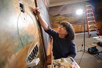 Photo of Joan Gorman repairing a mural.