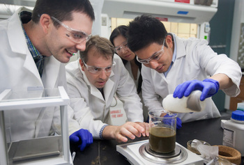Photo: Jamison Watson, Troy Runge, and Kim Huong Pham examine a manure sample being prepared for separation by Zong Liu.  Photo credit: Matt Wisniewski