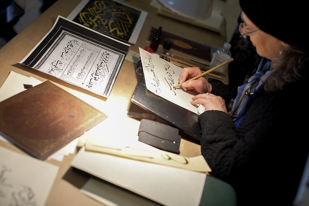 Photo: Calligrapher writing Arabic letters