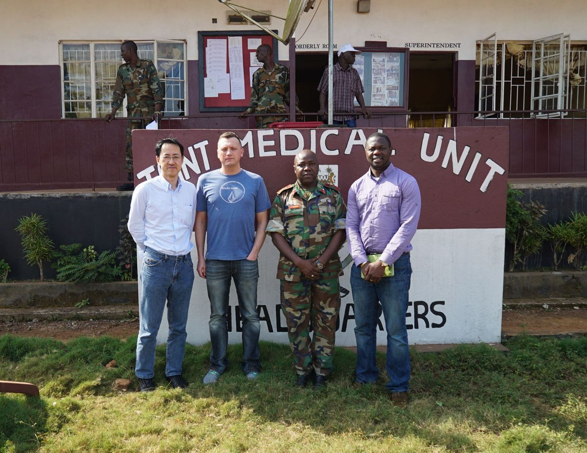 Photo: UW–Madison's Yoshihiro Kawaoka, Peter Halfmann and Alhaji Njai stand outside of a military hospital with Foday Sahr