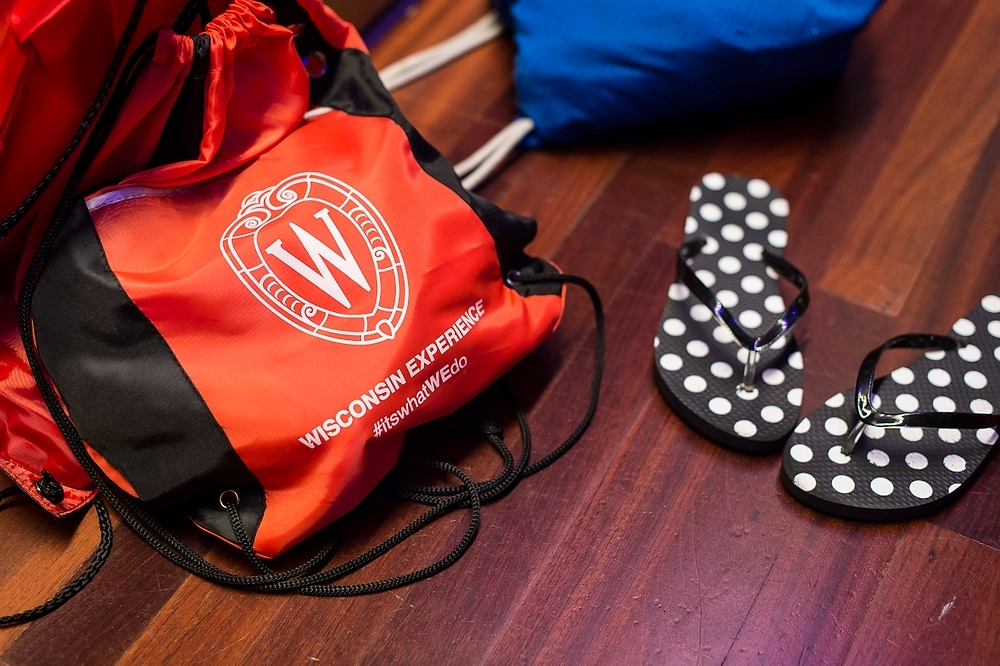 Photo: A Wisconsin Experience backpack and flip flops sit to the side as  students learn ballroom dance steps.