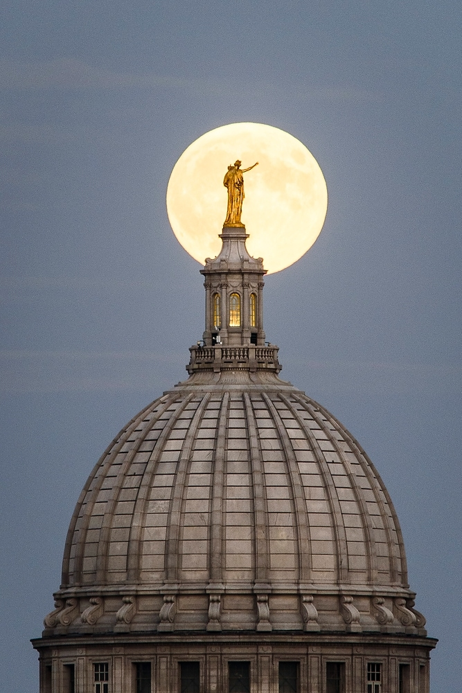 Photo: Closeup of moon behind statue