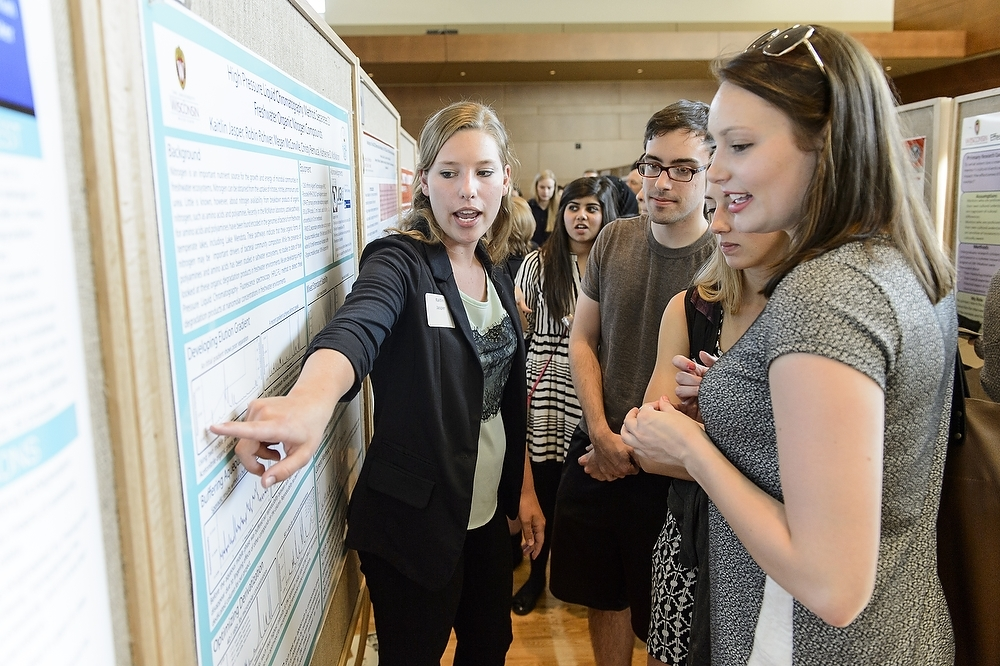 Photo: Student pointing to research poster