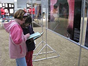 Photo of two girls on a scavenger hunt, standing in front of astronomy-related images.
